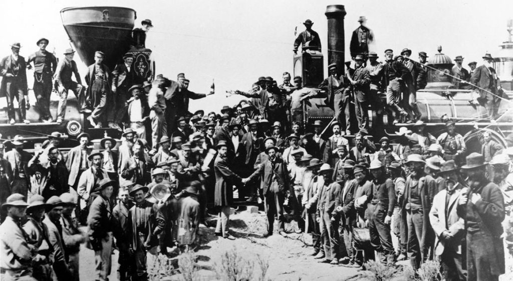 Railroad officials and employees celebrate the completion of the first railroad transcontinental link in Promontory, Utah, on May 10, 1869. The Union Pacific's Locomotive No. 119 (right) and Central Pacific's Jupiter edged forward over the golden spike that marked the joining of the nation by rail. | Andrew J. Russell creator QS:P170,Q4757433 Restoration by Adam Cuerden, East and West Shaking hands at the laying of last rail Union Pacific Railroad - Restoration, marked as public domain, more details on Wikimedia Commons